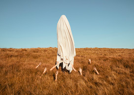 This is a colour landscape image of a flat grassy mountain top that meets the horizon halfway up the photograph. Above this section is an expanse of an aqua blue and cloudless sky.  The sun beats down on the scene and illuminates the grass in attractive warm golden light. In the centre of the image is a tall figure cloaked in white fabric that appears to be levitating a few inches above the ground. The fabric that conceals the individual underneath is wrinkled and bunched up as a gentle wind blows. Two arms beneath the figure protrude from the red coloured grass and pull at the edges of the sheet as though they were keeping the figure from floating away. Six other pale hands rise up from the grass, all outstretched and reaching towards the tall figure.