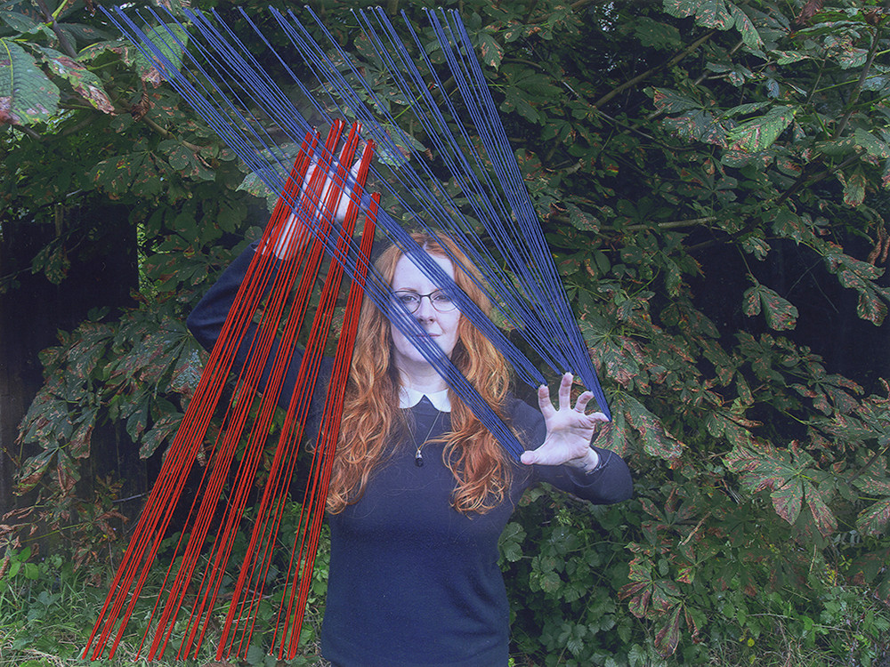 The photograph is of a ginger haired woman wearing a black jumper with a white collar stood in front of a tree with green leaves. Her arms are outstretched; one above her head and the other below. Red thread has been sewn into the photograph from the bottom left corner to her finger tips of her left hand. Her other hand has blue thread from the top left corner of the image down to her fingers.