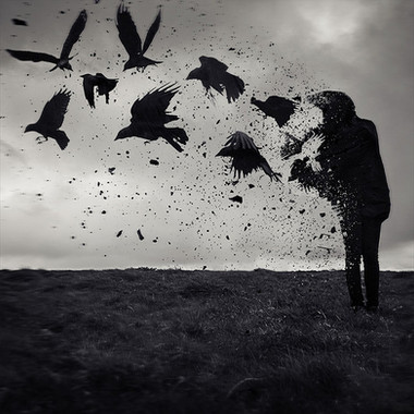 This square image is in black and white. The bottom third is of a dark grassy mountain top, with a moody grey sky behind. To the far right of the photo is the silhouette of a figure dressed in black. Large crows seem to be emanating and bursting out of the left side of the figure. Shattered fragments of her litter the air as if she disintegrates into pieces. The flock of crows are in flight and are moving away from her through the sky.