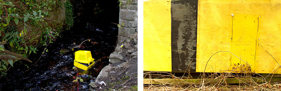Left: This is an image of a river with a bright yellow broken TV dumped in the middle. The back of the square TV is falling off and likely to be washed away. To the right is a wall that forms he side of a bridge and to the left of the river the bank is visible with green overgrowth growing and dangling into the water below. Right: The image is made up entirely of a bright yellow wall with only a long black wooden panel breaking up the scene. At the base, dead brambles lay on the ground.