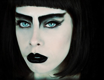 This is a landscape colour portrait of a woman's face. The image is very close up and as such the details of the woman's piercing blue eyes can be seen. The woman has black hair and a short fringe which frames the image in blackness. The model wearing gothic black make-up on her eyes and lips is very striking. The photograph has a faded blue and red tone, making it feel otherworldly.