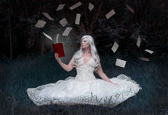 This is landscape image of a woman with white long wavy hair sat in a field of bluey green grass that is surrounded by tall trees of the same unusual colours. She is wearing a flowing white lace dress that extends out around her. In her one hand is a red book, her other is casually placed on top of her dress. Pages fly in the air around her, seeming to explode out of the book.