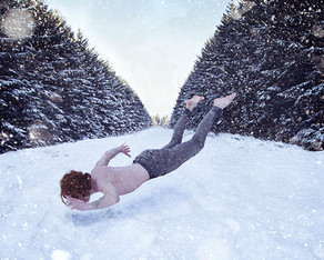 This is a photograph of a snowy scene of tall fur trees encroaching from the left and right side of the image, following the trail of a wide path into the distance. A man without a top or shoes on appears to be floating above the snow as if by magic. His auburn hair stands out against the tones of white snow. His arms are outstretched, attempting to cling on to steady himself as he levitates.