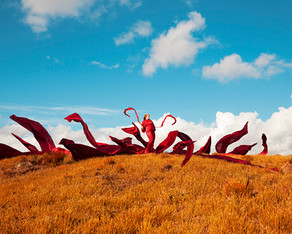 This is a colourful landscape photograph of an orange mountainside of grass set against a bold blue sky with small white clouds in the distance. In the centre of the image stands a woman with 15 lengths of fabric flying up in the air all around her.