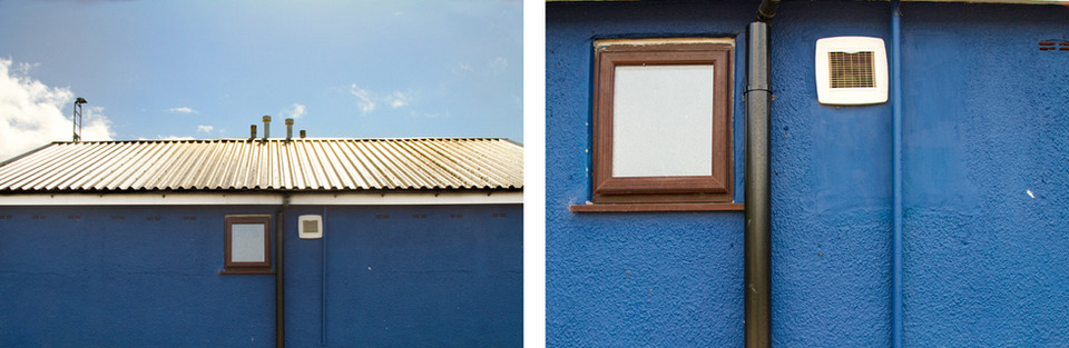 Both images are of the same building in bold and bright colours of blue. The image on the left is a far away image of a blue wall with two very small rectangular shapes in the centre; one is a window with a brown wooden frame and the other a small plastic white vent. Behind is a lovely blue sky with a puff of cloud in the left side. Four skinny chimneys rise above from the culver corrugated metal roof. Right: This is a close up image of the two rectangular shapes in the previous image.