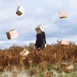 This is a square image of a woman in black jeans and jumper stood on a hilltop that is covered by brown ferns in an autumnal scene.  The woman has a lightly brown coloured cardboard box on her head, concealing her face. Around her are other cardboard boxes, some laying on the floor or in the ferns and others magically floating around and above her in the cloudy sky.