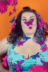 This is a portrait colour image of a woman that is stood in front of a bright orange background. The model has black and purple hair and is wearing an aqua blue dress with a floral design. She image is a headshot, with it cutting off at her chest. She is pulling an amusing face as a purple butterfly is perched on her nose. Around her float pink and blue butterflies in the air.