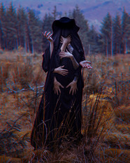 This is a colour self portrait image of a tall figure draped in black fabric and a black wide brimmed hat in an autumnal landscape of brown overgrowth and distant pine trees. The figure has 8 arms that poke from out of the black cloak, each in a different position. Two are wrapped around the figure's neck, two are hanging down towards the ground, another pair clutch at it's chest and the final two hands are both raised slightly in the air.  The image has an unusual 3D effect with red and blue edges around the outlines of the figure and trees.