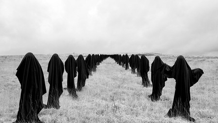 This is a black and white landscape photograph of a barren flat grassy landscape which meets a clouded sky around halfway up the image. On both the right and left hand sides of the picture are ghostly figures in black stood facing the camera. they leave a gap of around 2 metres between them. Behind these two figures are rows of other black cloaked figures that stand still, also facing the camera. These rows trail off into the distance and end where the landscape meets the sky. At the very end of the rows, they are mere black specs. Each figure is 2 metres distance from the other.