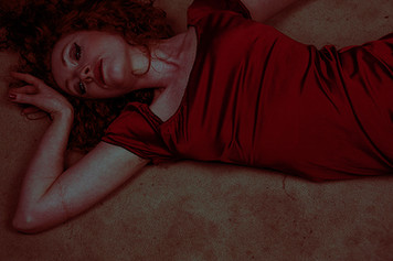 This is a landscape image of a woman laying on the floor in a  tight blood red dress. Her arm is raised to her head and she is looking directly up at the camera. There are unusual tones of green and red in this image, as if altered or shot with expired and out of date film. The model is cropped from her lower waist upwards. The floor in which she is laying on is brown carpet.