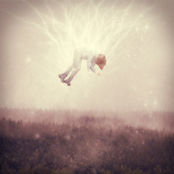 This is a square colour image of a woman floating in the sky. Beneath her are tall pine trees. Bolts of electricity emerge from the top section of the image and move towards her body, as if she was creating some kind of static charge. The image is a pale orange and brown in tone, making it feel dream-like.