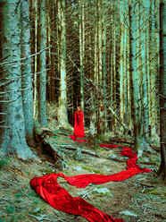 This is a portrait colour photograph of a woman stood in the centre of a forest with tall pine trees in an unusual hue of aqua blue and green. The figure is small in this landscape and is wearing a red cloak that snakes around the forest floor and leads back out to the bottom section of the image.
