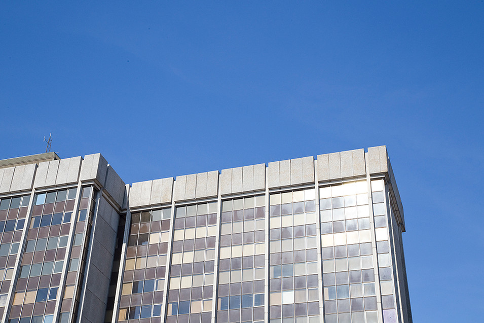 This is a photograph that has been taken looking upwards to a tall office building made up from rows of glass windows and brown panels. Above the building is a bright blue cloudless sky. The sunlight is reflecting off the building in the right side of the image. The image has been taken at an angle so that the shape of the offices cut a slight diagonal line into the sky.