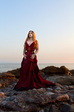 This is a portrait colour image of a woman stood on a rocky beach with a seascape behind her that extends out to a pale pink sky that moves into beautiful tones of blue. The womb is wearing a red corset and draped long skirt. Her hair is bathed in golden light as she looks away from the camera.