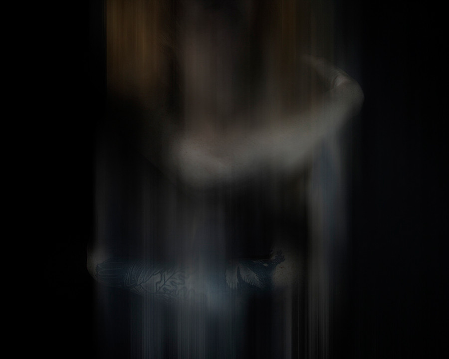 This image is very dark in colour with a black background. The image has been blurred as though the model is a ghostly entity. The only part of the model you can clearly see are two arms criss crossing each other, as though the figure is hugging themselves. Their faint outline bleeds vertically in blurred lines, or perhaps the figure is melting, disappearing.