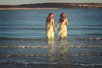 This is a colour landscape image of two women in yellow dresses stood in the sea. They are holding hands as their hair gently moves in the wind. This seaside scene shot in December seems cold and empty despite the two figures holding hands and showing each other warmth and affection. The sea is a shade of blue with tones of yellow from the sun's rays catching the crashing waves. In the distance, you can see land and the seaside town of Ogmore-by-Sea.