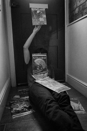 This is a black and white portrait image of a man laying on the carpeted floor in a corridor in front of a house door. His one arm on the left side of the picture is reached upwards with a hand ready to grasp at letters that are falling from the letterbox. Around him are other letters and small parcels on the floor and on his body.