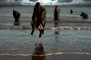 This self portrait image consists of five ghoulish black figures floating or stood in a blue sea. They are varying distances away front he camera, with the figure closest appearing to be levitating in the air towards the camera and viewer. A stormy sky can be seen in the background, setting a moody scene. A gentle warm light catches the white tones of the waves in the sea and colouring them in a pale yellow glow.