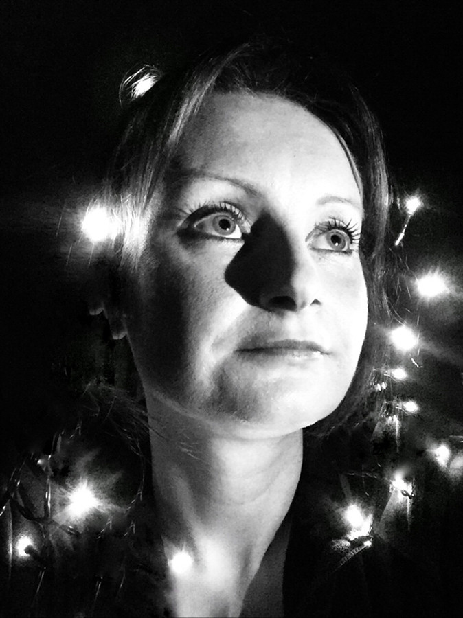This is a high contrast black and white portrait photograph of a woman's face and shoulders. Around her are pretty fairy lights that illuminate random sections of her hair and neck. Her face is bathed in brilliant bright light as she looks upwards to the right hand corner. A contented expression fills her face, as though the photograph was captured a moment before she broke into a smile or laugh.