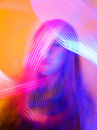 This portrait image is bright and colourful with tones of orange, pink and blue. Light trails move across the image in regimented lines and obscure parts of the image, leaving a certain mystery to the photo. A woman can be seen behind these swirling colours from the shoulders up. Only her right eye is in focus as she looks in the direction of the camera.
