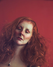 This is a portrait colour image of a woman from the shoulders upwards. A red background matches the red tones of the backcombed and messy hair of the female figure that dominates the photo. Her eyes are closed. Her skin is coloured in unusual tones and hues of pale aqua blue and pinky red, making the image appear out of this reality.