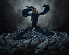 This is a colour landscape image of a girl with long ginger hair stood on a tall pile of rocks of varying sizes. She is dressed in a long black cloaked dress with two long lengths of fabric curling upward from her body into the air as thought hey had a life of their own. The sky behind is black with plumes of smoke and cloud behind the magical figure. The image has a slight blue tone, making it seem otherworldly.