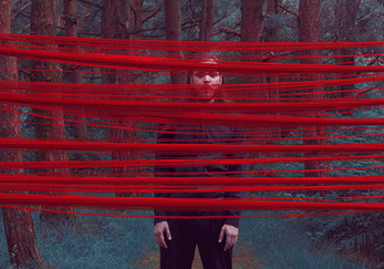 This is a landscape image of a forest scene with unusual tones of bluet green for the grass and red for the tall tree trunks that are scattered around the photo. In the middle of the image is stood a man wearing a black shirt and trousers. In front of him are red pieces of rope from the left to her goth side of the image that conceal sections of the image and his face and body.