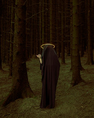 This is a colour portrait photograph of a figure draped in black cloth stood in a dark forest of tall pine tress with elongated trucks. The image has an eerie green glow about it which makes the scene feel suspicious. The black cloaked figure has a golden halo around it's head and a single arm protrudes from the cloth and is facing upwards, as if pointing to something unseen and out of shot.