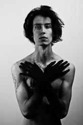 This is a black and white portrait shot of a man stood in front of a white and grey background. It is cropped from his lower waist upwards. The model is topless with his hands painted black as they are placed on either side of his chest. He has jaw length black hair and pale skin. The heavy lighting used in this image creates dark shadows that contrast against bright white areas where the light hits the one side of his face. He is also looking directly at the camera.