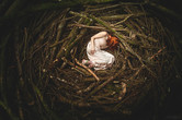 This self portrait image is titled, 'A Safe Place.' This is a photo of a large nest that takes up the entire image. Layers of branches ranging from thick blocks down to small twigs are arranged in a  circular pattern. A girl is laying down in the middle in a foetal position with her face unseen. She is wearing a cream coloured floaty dress and appears to be at peace or asleep. The light is focused on this area of the figure on the floor, drawing attention to the vastness of the surround nest.