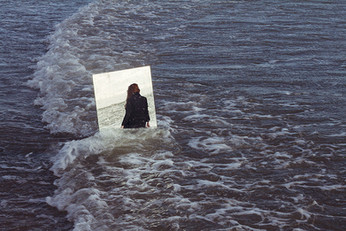 This is a landscape image of a seascape. A shallow wave laps against a rectangular mirror that is standing up in the water. The sea is a dark shade of blue mixed with white bubbles of foam. In the mirror, you can see a human figure dressed in black with long auburn hair. Their head is turned away from the mirror so we cannot see who they are but it appears as though they are walking out into the depths of the sea.
