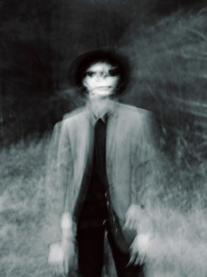 This is a portrait black and white photograph of a man wearing a pale grey suit jacket, black hat and matching black jeans and shirt stood in a field with a dark background. He has 'corpse' make up on which is like a skull. The areas of his skin around his mouth, nose and eyes are painted black and stand out against his Winter pale skin. The image is blurred with double exposures of the man in a slightly different position and therefore seems a bit creepy.