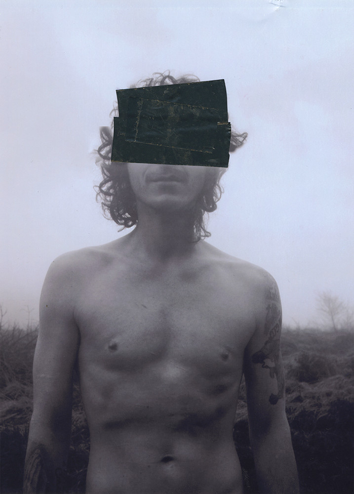 This is a black and hits portrait image of a man stood outside with a grassy mountainside behind him. He is facing the camera front on and isn't wearing a top. In the image, his head, chest and torso is shown. His skin is covered in goose pimples, as though he were cold. His face is partially concealed by two black sections of tape that have been placed on top of the printed photograph.