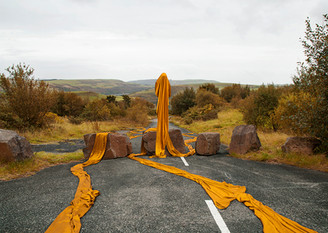 This is a colour landscape image of a road leading from the camera out into the distance. The road narrows at it progresses through the image, firstly spreading across the entire bottom section of the photograph and finally disappearing in the middle part of the picture. Surrounding the road on both the left and right sides are trees, shrubs and grass in Autumnal colours of oranges and yellows.  The road is blocked in the middle section of the photo by six large brown boulders. Stood upon one of the boulders in the centre of the picture is a yellowy-orange cloaked figure that is facing the camera. From the ghostly figure are two long lengths of fabric that snake and curve behind into the distance and lead in front in the foreground. The two long threads of fabric behind the figure wind around the road and up to the bottom left and right corners of the image. The figure's head is tilted downward, as if saddened or tired perhaps. Behind this unusual scene are mountain tops with forests, farmer's fields and slag heaps of industrial waste from the coal mines of the past. A small village with terraced houses clings to the length of a valley wall suggesting that these hills lead downwards to more urban areas.