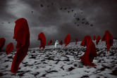 A snowy landscape scene in a field with a gloomy and stormy sky behind sets an atmospheric scene. Numerous red floating cooked figured stand in the image, appearing to be facing different directions and without cause. A single white cloaked figure levitates in the centre of the image, separate form the others and looks directly towards the camera. Crows fly in the distance behind this scene.