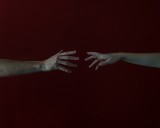 This is a photograph of two hands, reaching out to each other from either side of the image. The background behind is dark red and black. The outstretched arms are lit in an unusual gluey-green tone. The hands are seeking each other but do not touch.