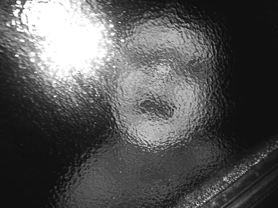 This is a high contrast black and white landscape image with deep blacks and bright whites of a distorted face behind a marbles window pane. The window gives the face a surrealist and pixilated look, so we are unable to recognise the face, only the blurry feature of a mouth, set of eyes and a nose. To the left side of the image is a bright white blob of light, making the image seem even more strange and creative.