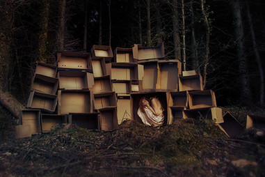 This self portrait image is titled, 'Caged.' The photograph is of a woodland area with a of mass of cardboard boxes stacked on top of each other on the ground forming a long wall. The boxes are bathed in golden sunlight and stand out against the dark forrest behind. A girl in a peachy cream coloured floaty dress is sat in one of the boxes with her hands over her head as if in distress or trying to comfort herself.