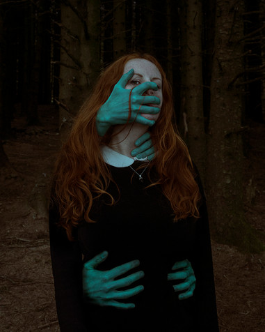 A moody portrait of a woman with long ginger hair stood in a forest. Four creepy looking greeny-blue hands grab and cover her face and body as if holding her in place. However, the woman's eyes are visible and she is looking directly into the camera.