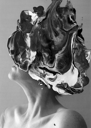 This is a portrait photo of a woman's head and neck. Her face is tilted to the side so that the angular shadows of her collar bone and jaw can be seen. On top of the photographic print is a layer of paint in swirly patterns of white, grey and black. This paint conceals the face of the model so that we don't know how she's feeling. This blob of paint stretches out in a circular shape and covers her hair also.