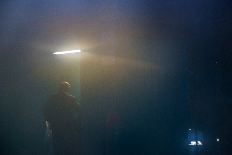 A hazy night time image of a male figure walking into a turquoise blue train station shelter, trying to escape the looming rain and misty weather. A bright white light illuminates the top of the gentleman's head above him.