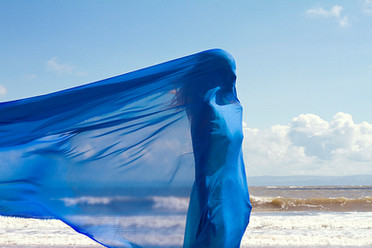 This is a landscape image of a woman cloaked in a sky blue long piece of fabric that is blowing in the wind outwards to the left side of the image behind her. In the background is a seascape and blue sky with small whet clouds forming above the horizon which is a third of the way up in the picture.