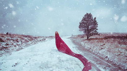 This is a landscape colour image taken in the snow. The landscape scene is of a winter's day during a blizzard. A person stands far away from the camera in the centre of the frame with a red cloak wrapped around her which snakes though the image, eventually leading back towards the camera on the right hand side. The girl is looking directly into the camera, giving the image a slight confrontational feel. She has pale skin and ginger coloured long hair. A singular tree is stood to the right of her in an otherwise unremarkable and lonely landscape.
