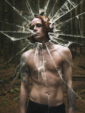 A man stands with his eyes closed and his chest bare in a darkened forest of tall fur trees. As the viewer, we're looking in through shattered glass with shards broken and reflecting a distorted version of the image. The man has long auburn hair and pale Winter skin. A tattoo adorns each arm; hands held together in prayer and the other of Owain Glyndwr on horseback.
