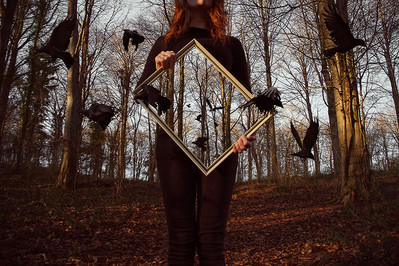 This self portrait image is titled, 'Hollow.' This colour landscape photo is of a forest scene in Winter with bare trees and warm orangey brown tones of fallen leaves on the floor. A girl dressed in black is stood holding a gold picture frame in front of her chest. The frame is empty inside, showing only the forest scene behind and not the torso of the girl as you'd expect. Black crows in flight emerge from the emptiness in the frame. The figure's face is unseen, instead the image is cropped so that we cannot tell what her mood is.