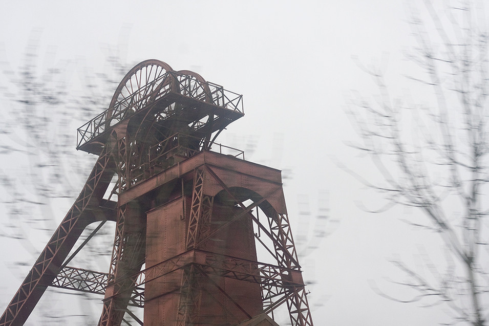 This is a photo of the top of the winding machinery used in the coal pits. It is red in colour with large wheels at the top. There are sections of criss-crossed mental framing to support the tall structure. In the foreground are blurred bare trees and behind, a white dull sky.