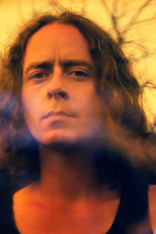 This is a format close up image exclusively n tones of orange and black. The photograph is a close up of a man with long jaw length curly hair that is looking directly into the camera. You can see the top of his black vest. Behind him are naked tree branches raising up to the orange toned sky.