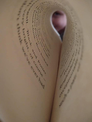This is a portrait colour photograph of a page in a book curled into an oval shape. The words of the page spiral around and become blurred and unreadable. At the end of the page is a blurred face looking down the length of the page.