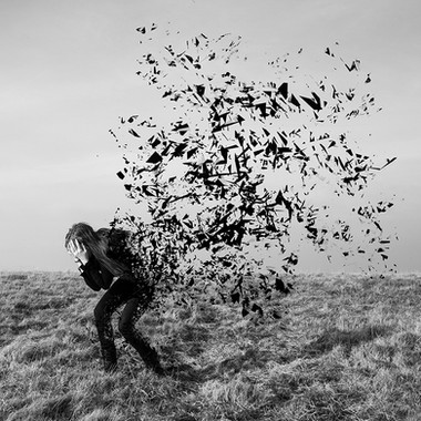 This is a black and white square shaped image. There is a grassy landscape pictures, taking up the bottom third of the image. Crouched, as if in pain stands a girl with her face in her hands. The back of her body is exploding into ribbons of black fabric, as if she was disintegrating. These pointed ribbons of material float in the air and seem to be carried away by a gust of wind.