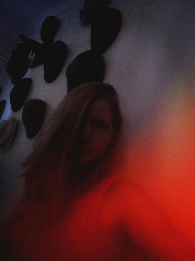 This is a dark colour portrait image of a girl with long blonde hair in front of a wall of hats. The bottom right corner of the image is lit in a wonderful red light which illuminates the girl in the image. She is staring directly at the camera.